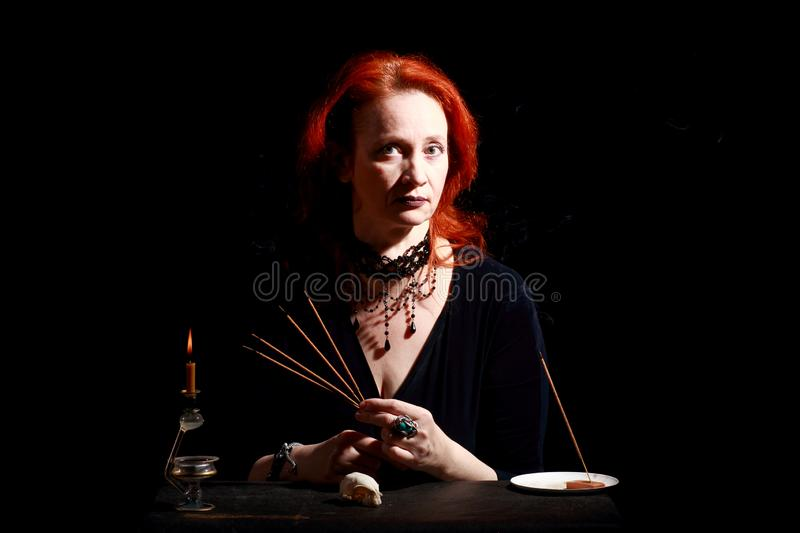 Witch light wizard candles. Fine emotional redhead witch with magical decorations and live expressions. Table with bird skull, candles and lamp. Black wizard stock photography
