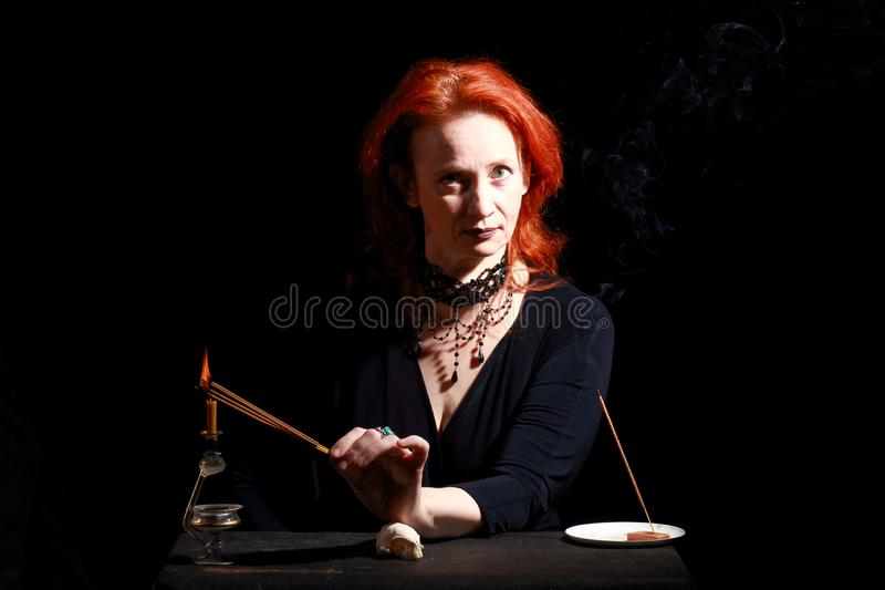 Witch light wizard candles. Fine emotional redhead witch with magical decorations and live expressions. Table with bird skull, candles and lamp. Black wizard stock image