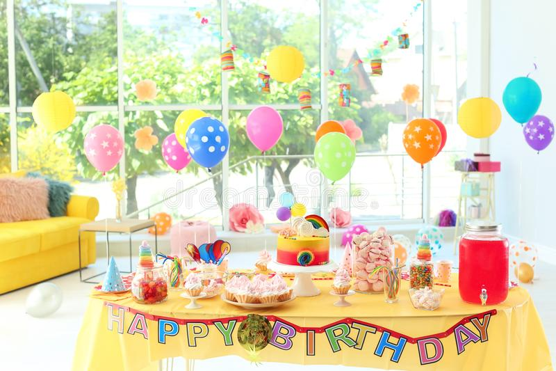 Table with birthday cake and delicious treats. Indoors royalty free stock photos