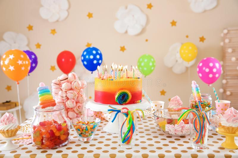 Table with birthday cake and delicious treats. Indoors stock image