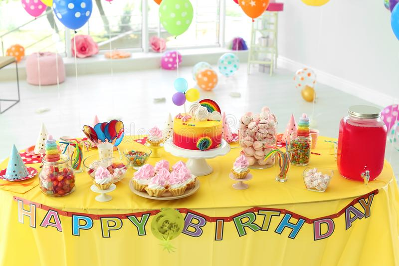 Table with birthday cake and delicious treats. Indoors royalty free stock photo