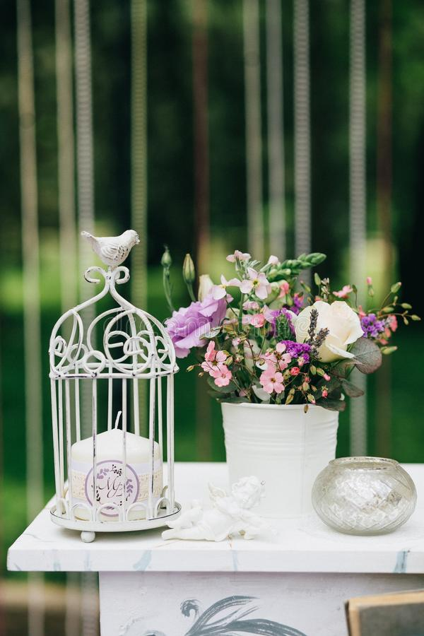 Table blanche décorative de vintage pour la cérémonie de mariage, décorée d'une bougie dans une cage avec un bouquet des fleurs photo stock