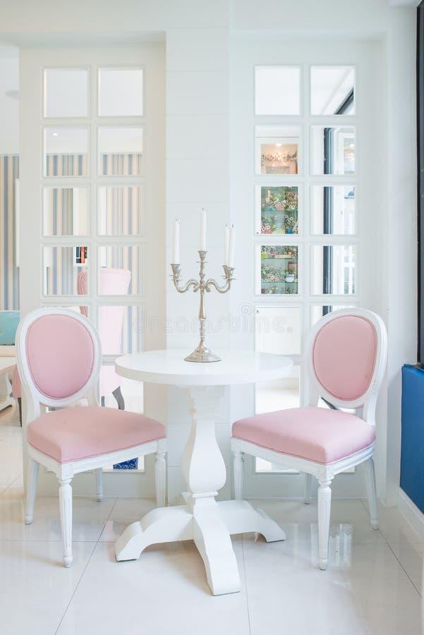 Table blanche et chaise rose avec la bougie sur la table dans le salon photographie stock libre de droits