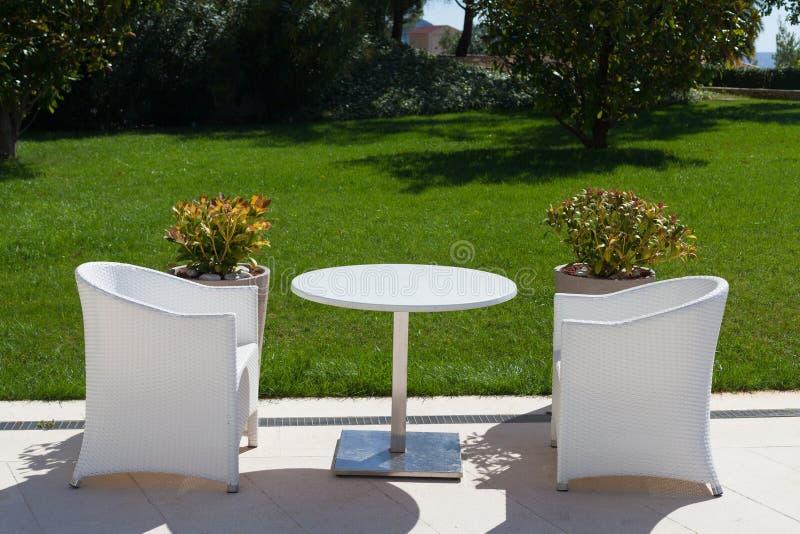 Table blanche et deux chaises dehors photo stock