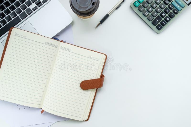 Table blanche moderne de bureau avec le stylo, le carnet en cuir, la calculatrice, l'ordinateur portable et la tasse de café image stock