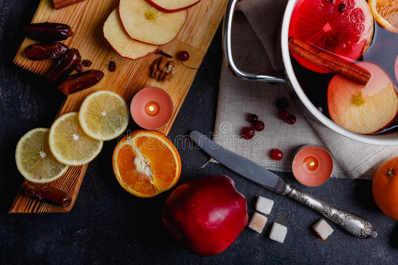 On a table is a board with dates and slices of apples and lemon, a knife and a pan with a mulled wine. View from above. On a dark table is a wooden board with royalty free stock photography