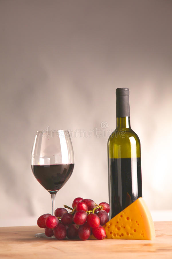 On the table a bottle of wine and a glass of.  stock photo