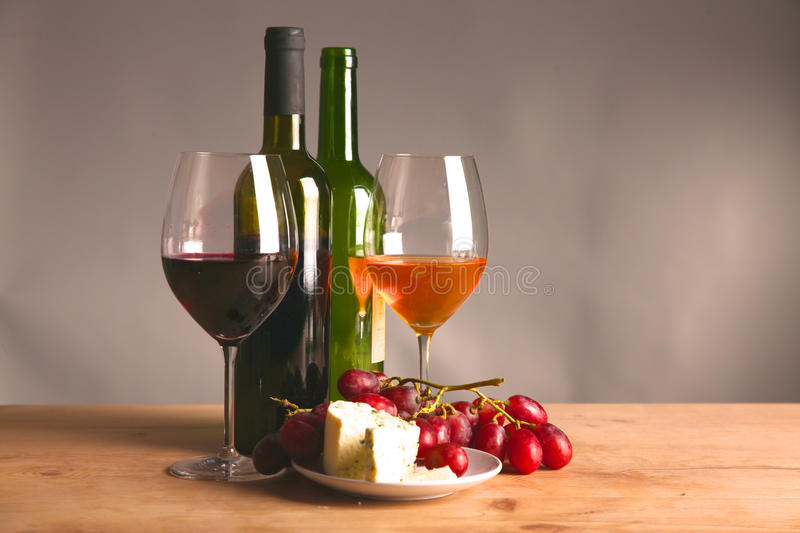 On the table a bottle of wine and a glass of.  royalty free stock photo