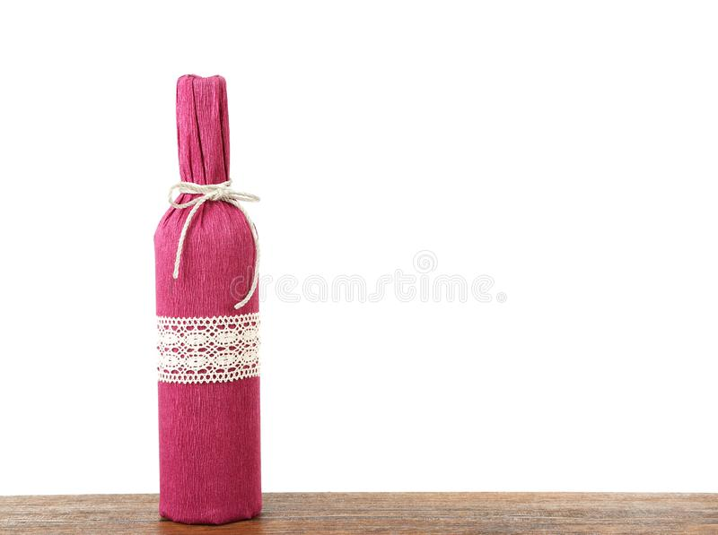 Table with bottle of wine in paper. On white background royalty free stock photo
