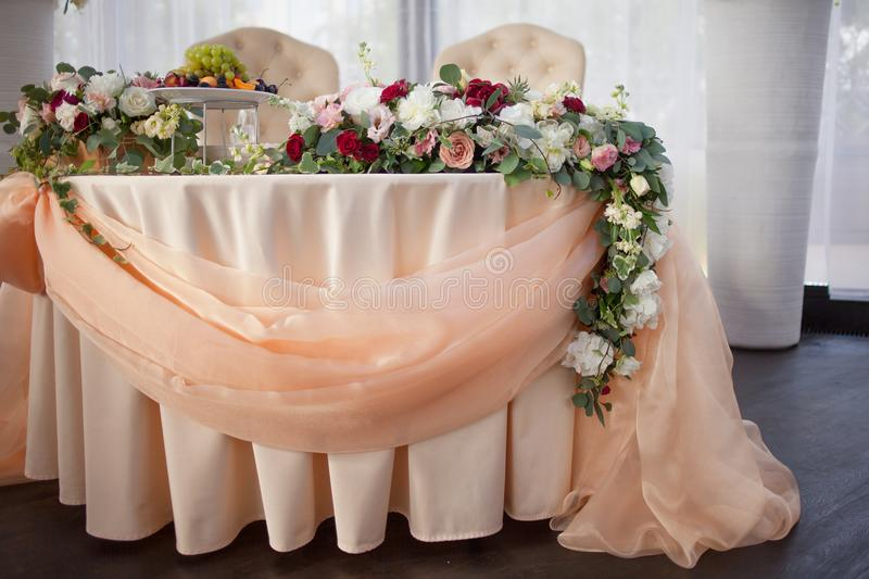 Table of the bride and groom in the restaurant. Wedding decor, flowers royalty free stock photo
