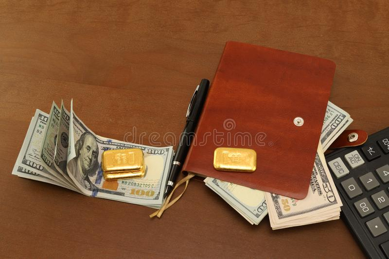 On the table is a brown leather notebook. Gold bars and cash dollars. Calculator and pen royalty free stock photos