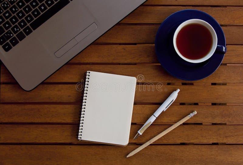 Table bureau avec ordinateur portable, tasse et toutes les propriétés importantes photo stock