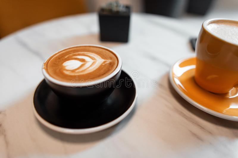 On the table in the cafe is a black cup with a hot latte and a yellow mug with cappuccino. Morning coffee break in the coffee shop.  royalty free stock photo