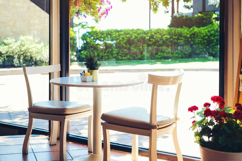 A table in a cafe with flower pot. Two empty chairs waiting for customers, interior with scenic seaside view out of the glass royalty free stock photo