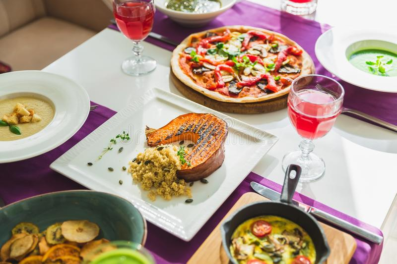 Table in cafe with vegetarian dishes - pizza, salads, pumpkin and fresh fruit drinks. royalty free stock image