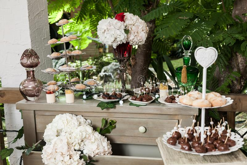 Table with cake, sweets and desserts for the reception of weddings and parties.  stock photography
