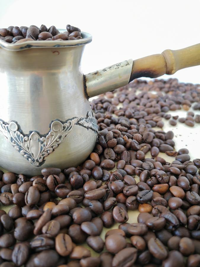 On the table is a cezve, filled with coffee beans. Other coffee beans are scattered around. On the table is a cezve,  with coffee beans.  coffee beans are royalty free stock image
