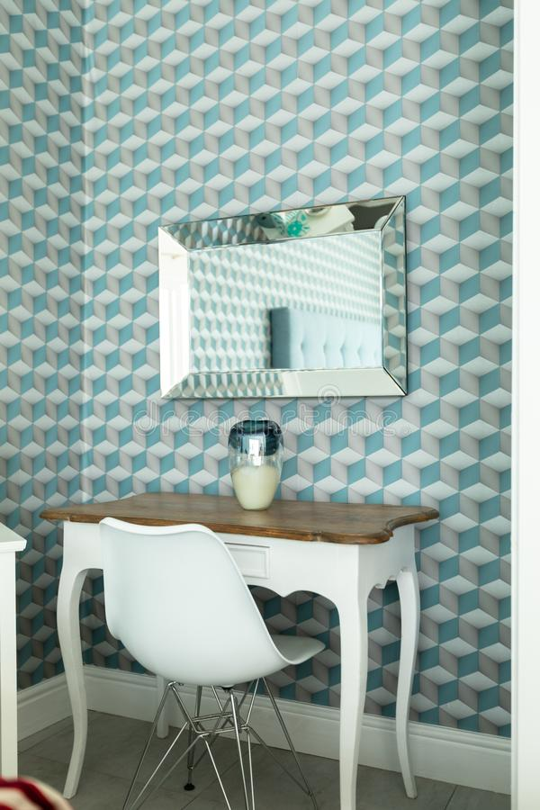 Table with chair and patterned wall. Side view of table with chair and patterned wall in modern house royalty free stock photo
