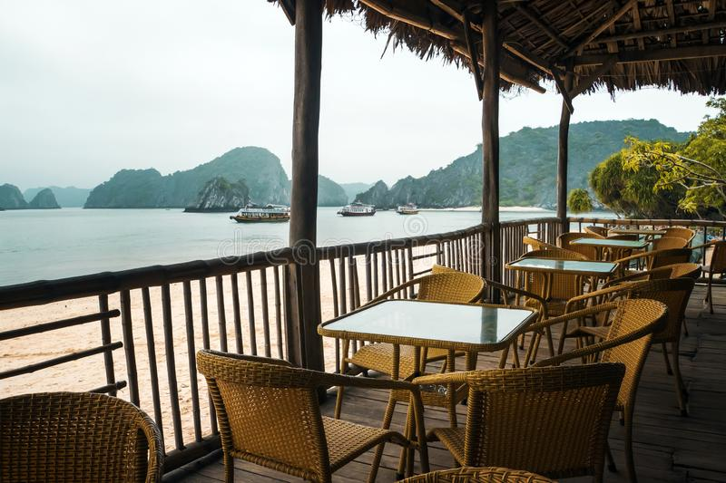 A table with chairs in a cafe under a canopy on the beach. View from the cafe on the Pacific Ocean. Ha Long bay stock images