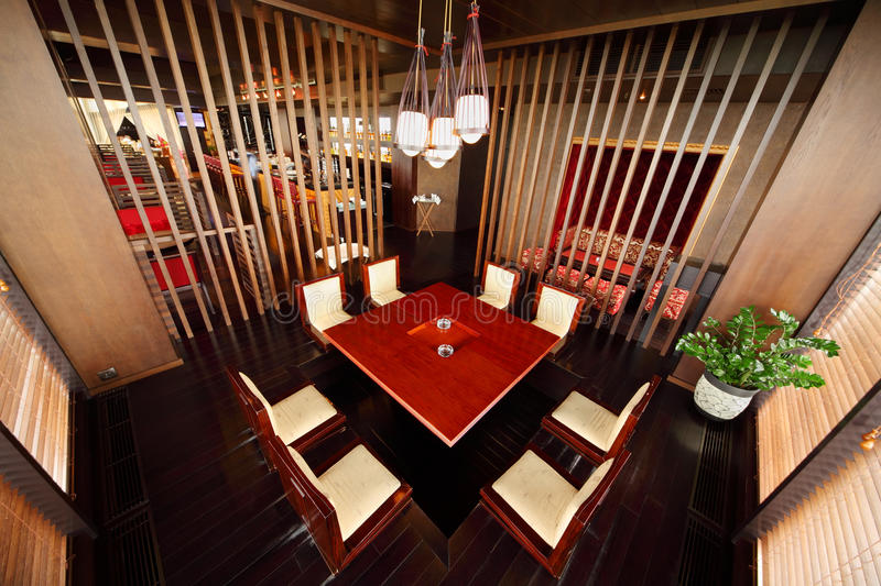 Table and chairs in empty restaurant. Square wooden table in deepening of floor and chairs in empty stylish restaurant royalty free stock images