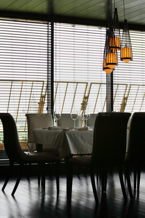 Table and chairs in empty restaurant. Table with white tablecloth and serving and chairs in empty restaurant stock images