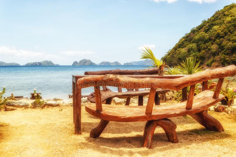Table and chairs on an exotic beach on a hot sunny day against the blue sea and sky royalty free stock photos