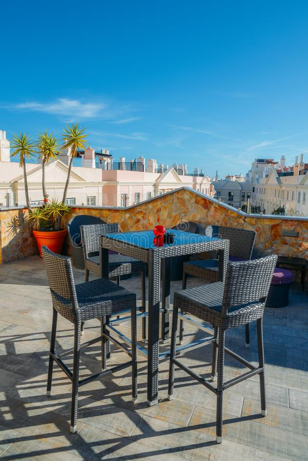 Table and chairs at a patio on a rooftop bar with sunny copy space background royalty free stock photos