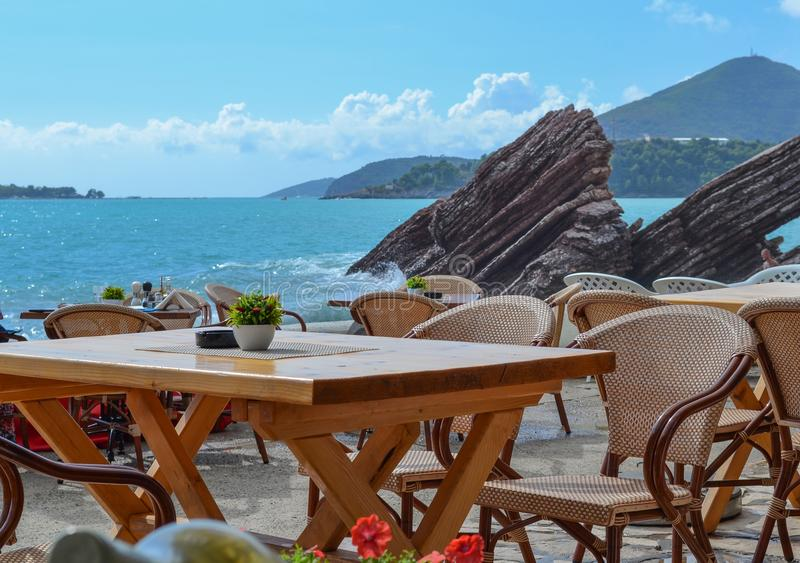 Table and chairs of the restaurant near the sea. Sunny day is summer. Without people. Montenegro royalty free stock photo
