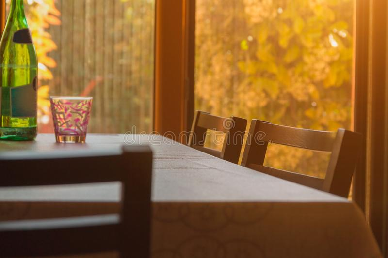 A table with chairs stands in front of a window in which the sun shines, home architecture, home comfort, artistic background stock photo