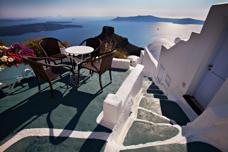 Table and chairs on a terrace overlooking scenic mediterranean seascape of Santorini stock photos
