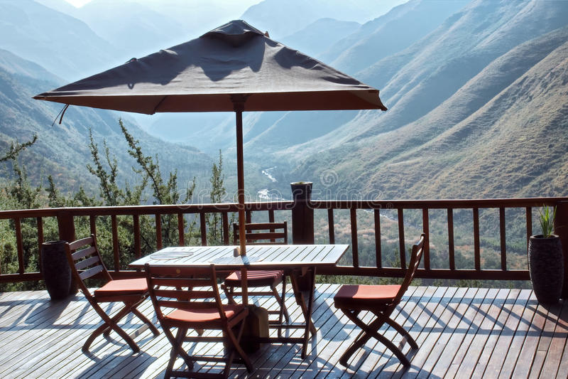 Table and chairs under umbrella on terrace against blue mountain stock photos