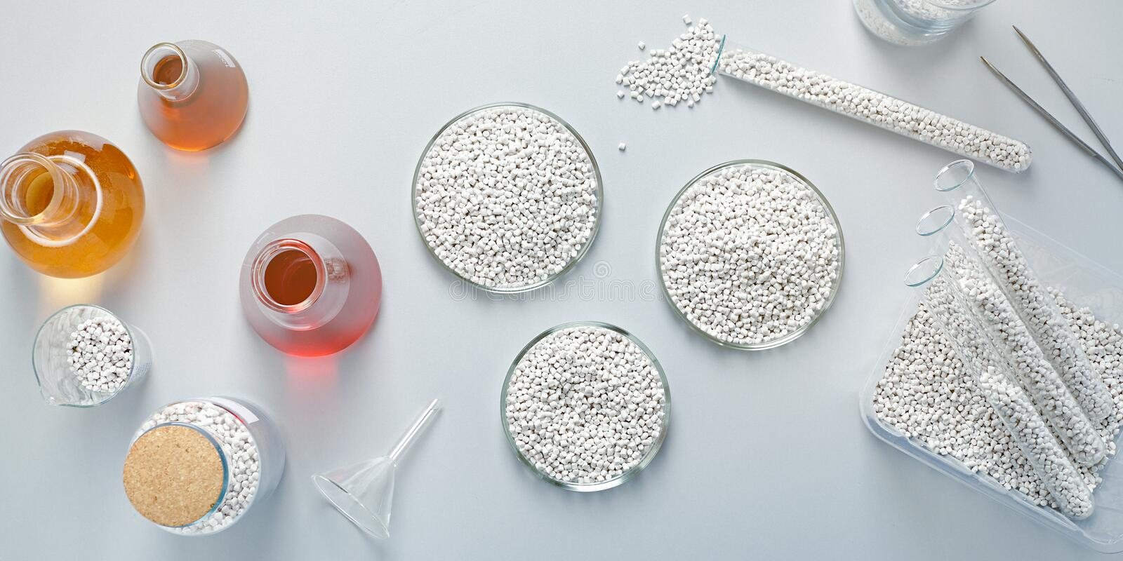 Table in a chemical laboratory with granules and chemical glassware. Top view of a table in a chemical laboratory with granules and chemical glassware at a plant stock image