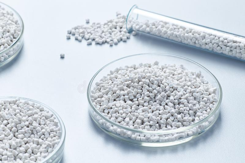 A table in a chemical laboratory with granules and chemical glassware. At a plant for the production of polymer products from white chalk polymer stock photo
