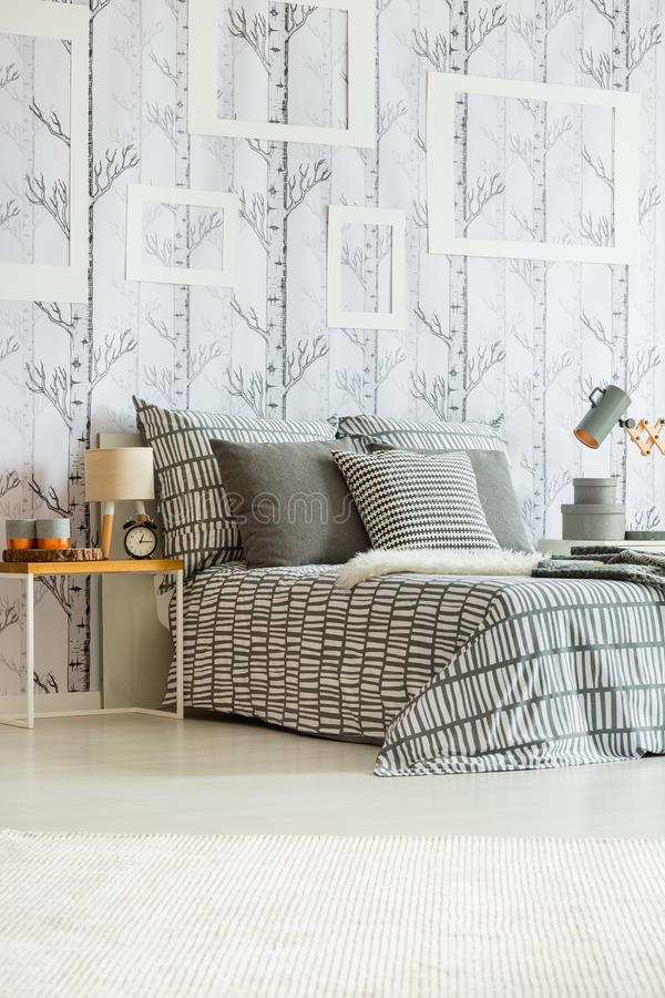 Patterned grey and white bedclothes. Table with clock, lamp and decorations standing by the bed with patterned grey and white bedclothes in room with mockup royalty free stock photo