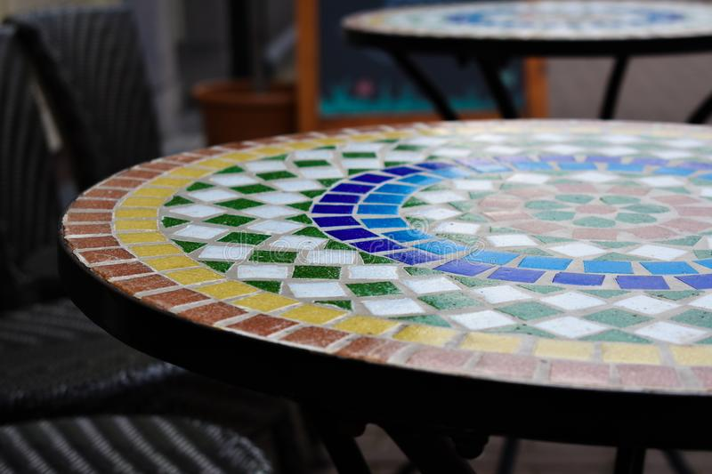 Colorful Table On A Terrace. Table with colorful stones on the terrace of a restaurant. Stones in the colors red, orange, dark blue, light blue, green and white royalty free stock photos
