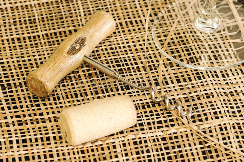 On the table, corkscrew and wine cork. And glass close stock images