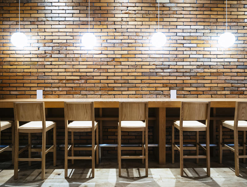 table counter bar with chairs and lights brick wall background stock