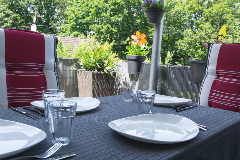 Table couverte de balcon avec les plats blancs photographie stock
