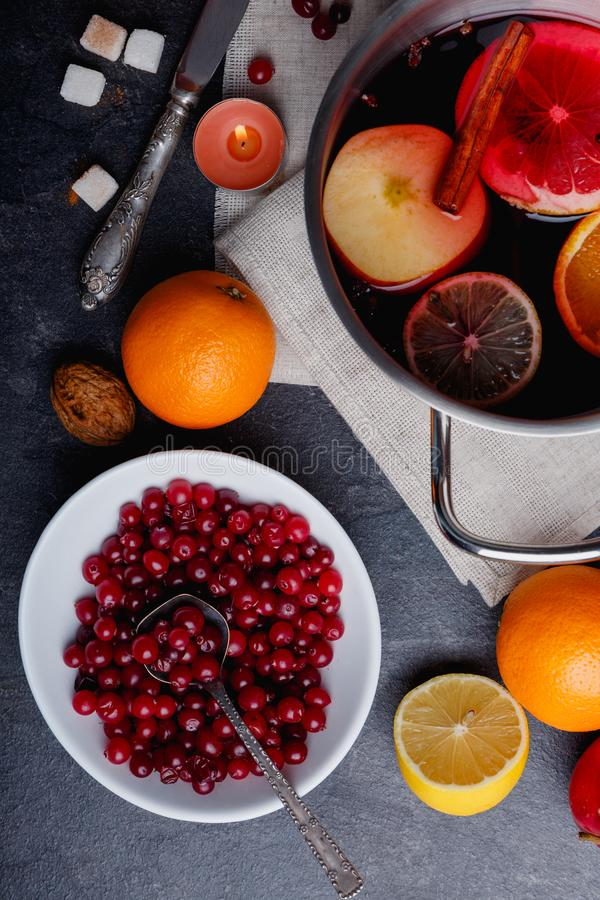 On the table is cranberries, a pan with a mulled wine, an orange and a lemon. View from above. On the table is a white deep plate with cranberries, a metal pan stock photography