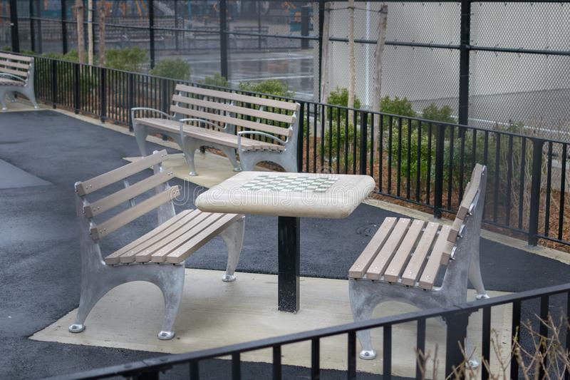 Table d'échecs et bancs vides, en parc à Williamsburg, Brooklyn, un jour pluvieux, New York City, Etats-Unis photos libres de droits