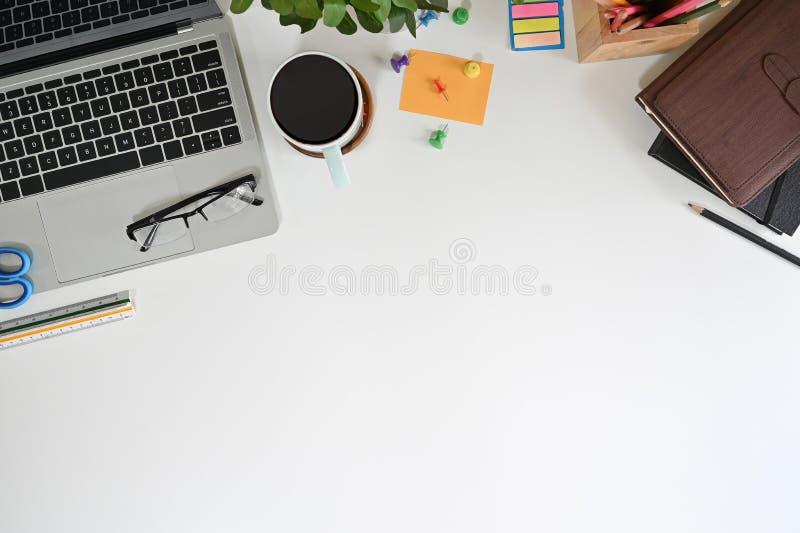 Table d'affichage supérieure du bureau avec ordinateur portable, café, verres et fournitures de bureau photo stock