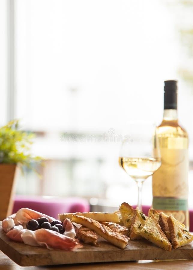 Table d'apéritifs avec les casse-croûte et le vin italiens d'antipasti en verre image libre de droits