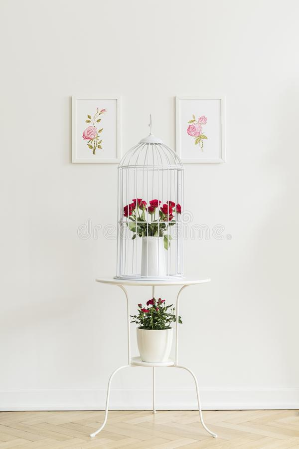 Table d'extrémité en métal blanc avec les roses rouges fraîches se tenant sur le herringbo photos stock