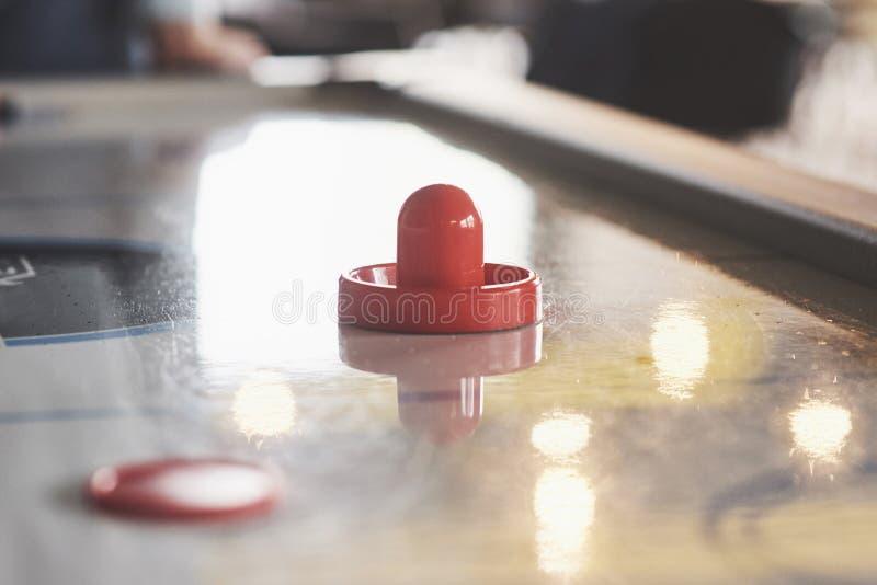 Table d'hockey d'air avec l'éclairage de fenêtre et le bâton de hockey rouge de jouet photos stock