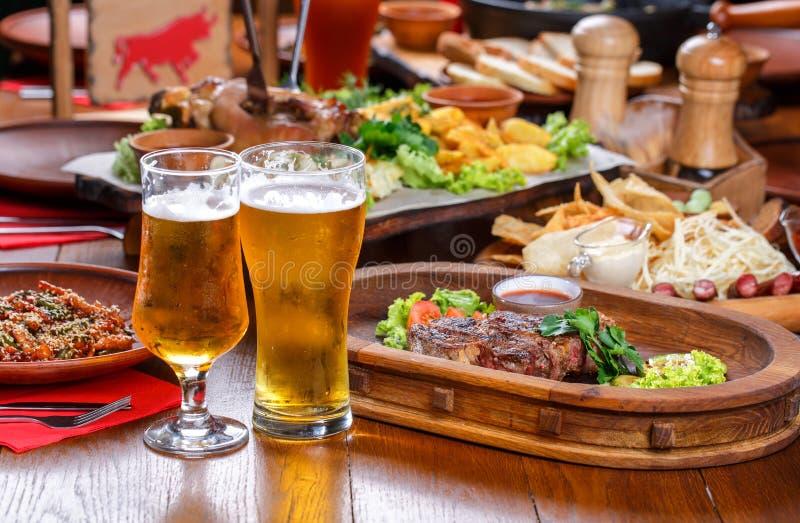 Table de bière dans le bar Bifteck chaud avec de la sauce et des légumes image libre de droits
