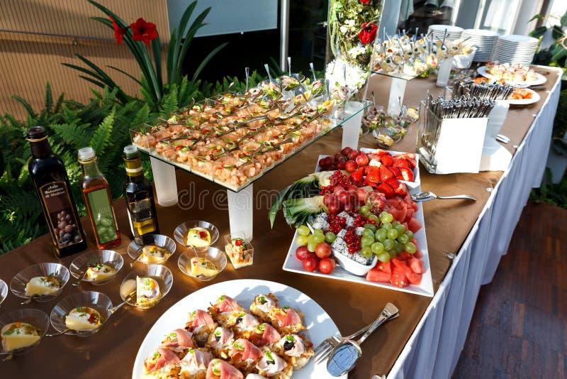 Table de buffet complètement de nourriture dans de petits plats et un plateau de fruit photographie stock