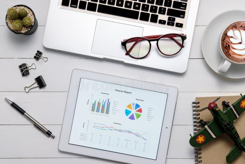 Table de bureau avec des données financières sur le comprimé d'écran photographie stock