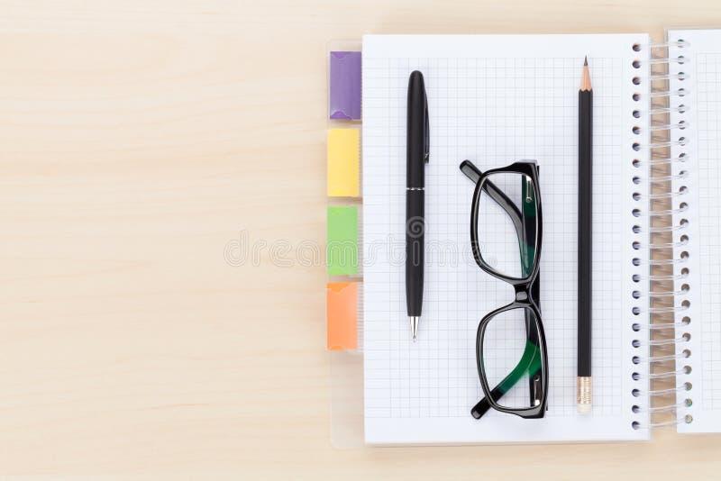 Table de bureau avec des verres au-dessus de bloc-notes, de stylo et de crayon image libre de droits