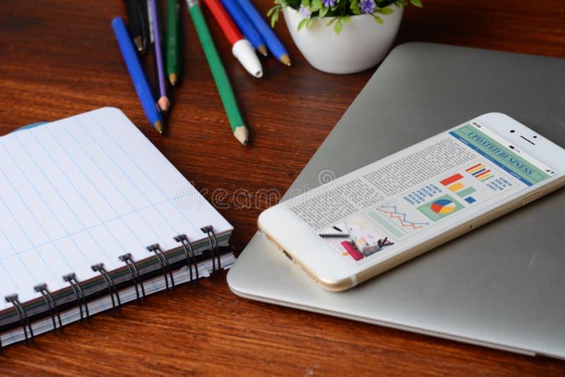 Table de bureau avec l'écran de smartphone avec des statistiques au sujet de croissance de l'entreprise photos stock