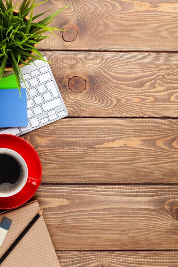 Table de bureau avec l'ordinateur, les approvisionnements, la tasse de café et la fleur images stock